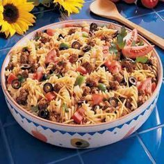 Taco Pasta Salad 1	package (16 ounces) spiral pasta 1	pound ground beef ¾	cup water 1	envelope taco seasoning 2	cups (8 ounces) shredded cheddar cheese 1	large green pepper, chopped 1	medium onion, chopped 1	medium tomato, chopped 2	cans (2-¼ ounces each) sliced ripe olives, drained 1	bottle (16 ounces) Catalina or 16 ounces Western salad dressing
