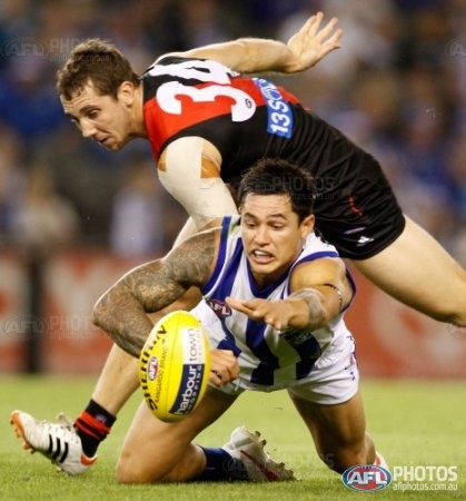 North Melbourne's Aaron Edwards and Essendon's Kyle Hardingham compete for the ball during the AFL Round 01 match between the North Melbourne Kangaroos and the Essendon Bombers at Etihad Stadium,
