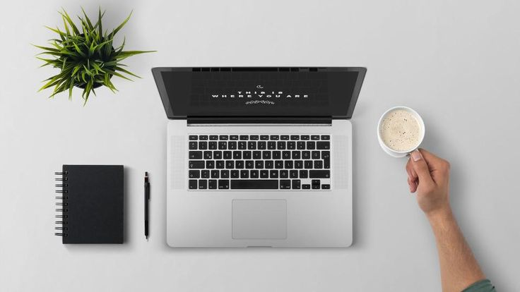 MacBook laptop on a white and clean desk next to a black notebooks, a pen, a…