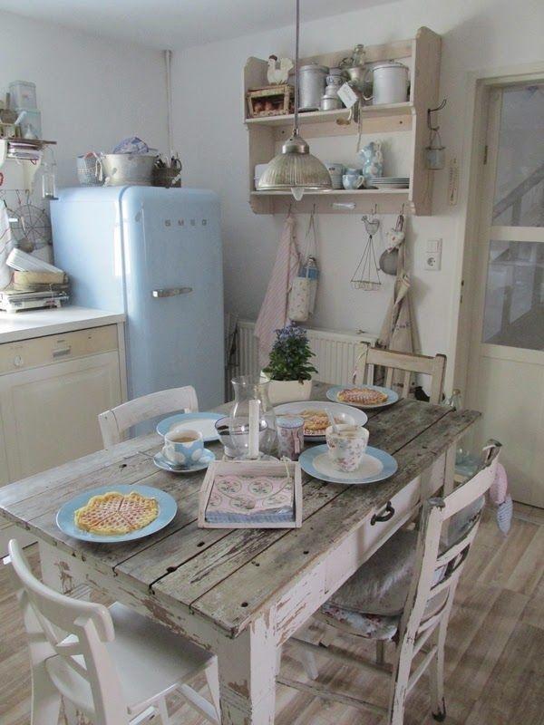 Ein alter Esstisch mit passenden Wandregalen macht deine Küche urgemütlich. Moderne Elemente wie der Kühlschrank oder das Geschirr sind ein moderner Stilbruch!