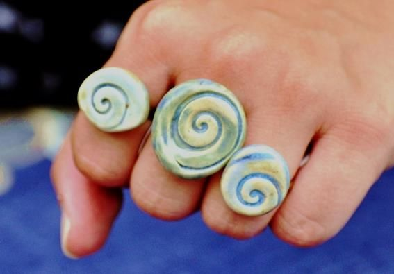 """Chunky Spiral Ring in Blue    One of a kind spiral seashell design stoneware ring, glazed in colors of sand and water. (See largest ring in photo).    Bring warm thoughts of beach days to mind wherever you go!     Measures 1.25"""" (3.2 cm) across.     Ring band has an antique bronze finish with adjustable size.    Casual and fun Boho style.    Shop now @ www.live-love-art.com"""