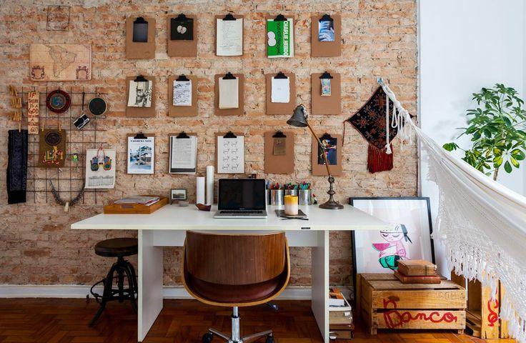 Home office com parede de tijolinho e pranchetas para colocar recados e recordações.