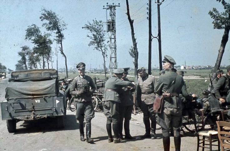 On the outskirts of Dunkirk, German officers confer by their vehicles at the roadside before moving into the town