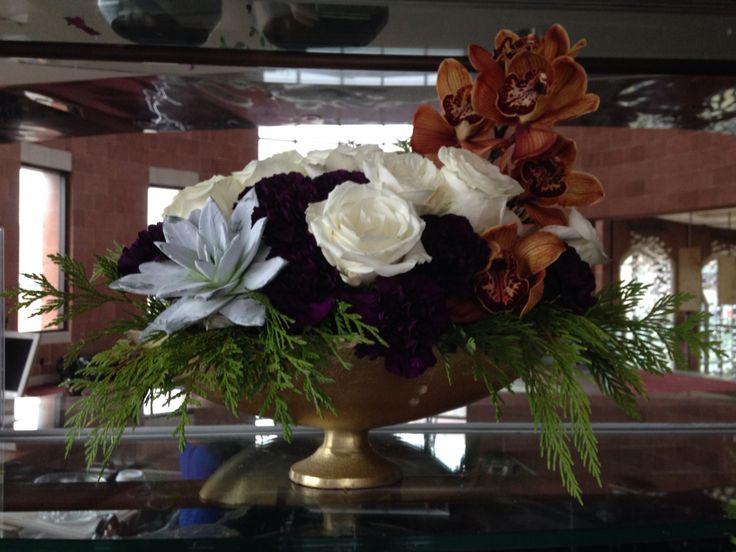 Christmas arrangement: gold orchids, white roses, purple carnations, succulent