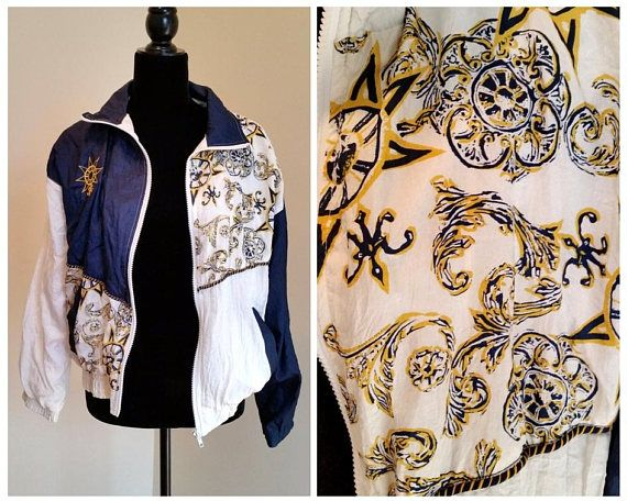 vintage 1980s lined windbreaker/ retro jacket white and blue patchwork colorblocks with gold and blue compass motif print zip up front, elastic wrists and waist, 2 front pockets make: westside connection material: nylon, polyester, cotton vintage size: small shoulders: 22 pit to pit: