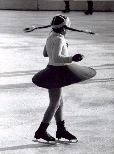 Schaatsen. Meisje met vlechtjes draait pirouette op de schaats. Plaats onbekend,…