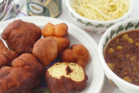 Traditionally pieces of bread dough was was fried in fat, hence the name vetkoek (fat cake). It is a quick alternative to baking bread. Vetkoek goes well with curried mince and soup.