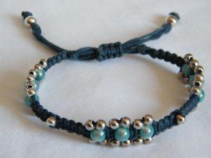 Macramé armband, uitgevoerd in donkerblauw wax-koord met aqua 3D-kralen. Aan de zijkant voorzien van kleine kraaltjes in zilver van 3mm. (bestelnr. MMP-005) De prijs van deze armband: € 15,95