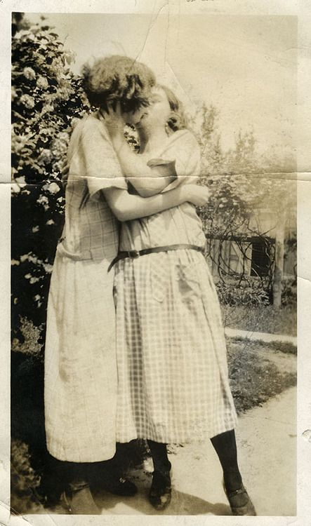 Obviously 1920's. I want to know city,area where  this was taken. How is it that these gals felt free of recrimination to have pic taken on the front sidewalk ( you can visualize the pavement, & neighbor's vine-covered porch ) ? Were they visiting relatives &  therefore would never fear  being ostracized by the community ?