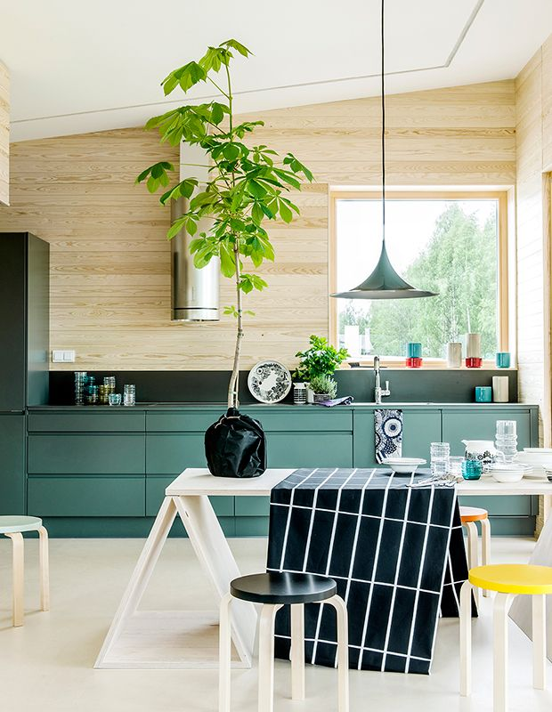 In true Scandinavian form, this funky kitchen boasts blonde woods, leggy furniture and a few quirky touches — like a giant plant on the kitchen table and flat-front cabinets in a saturated teal hue.
