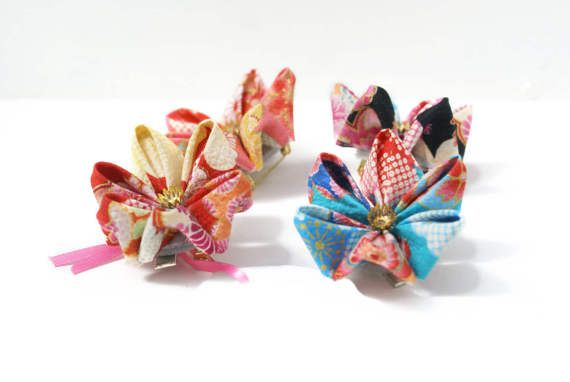 The Japanese kimono print on this kanzashi hair clip will have you squeeing with joy! Choose whether you would prefer it in a blue, black, pink or red colourway each featuring a drift of colourful cherry blossoms!  You can also choose whether you would like this as a hair clip, brooch, both a hair clip and brooch, meaning that it could be perfect for a Japan inspired wedding as bridesmaids hair flowers, or worn by the mother of the bride as an elegant brooch.  Whether this is for you…