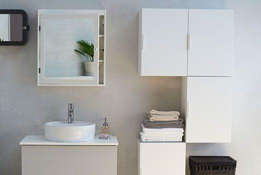 Et badeværelse med hvide skabe der hænger på væggen og et spejl over vasken. Godmorgenskab