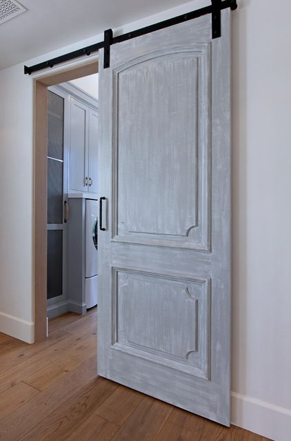Possibility for door to laundry room downstairs? I want a large opening. Current laundry room doorway is a little tight. There will be a half-bath nearby which will require a regular door. Maybe if the doors kinda match, the difference in the way they open won't matter. Mediterranean Hall by Jeri Koegel Photography