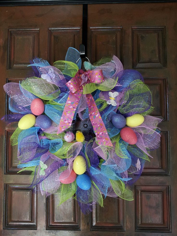 "Easter wreath - 4 colors of wire mesh, cut 12"" long, tied in half around a rounded coat hanger. Tie or hot glue embellishments."