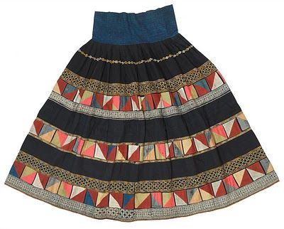A Yi minority skirt from Yunnan province, dating from around 1950. Indigo dyed cotton decorated with batik, with embroidery and with applique panels of old silk.