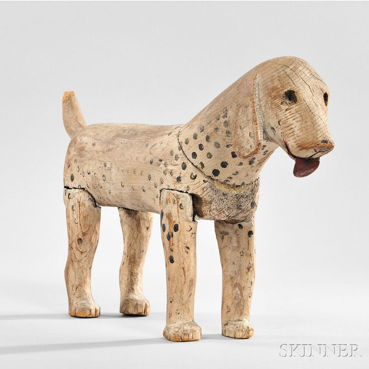 Carved and Painted Figure of a White and Black-spotted Dog, America, 19th century, the standing figure carved in seven pieces and joined, with separately carved red-painted tongue, old paint, (wear), ht. 10, lg. 19 1/2 in.