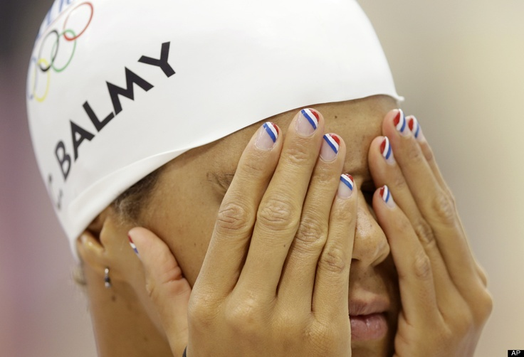 French swimmer Coralie Balmy wears nail polish in the colors of the national flag as she prepares for a practice session at the Aquatics Centre in the Olympic Park