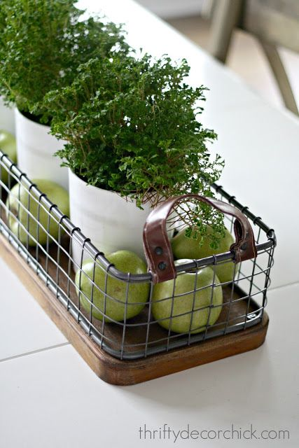 Easy spring centerpiece for your kitchen table, dining room table, or kitchen island.   Use green plants, faux apples, and a wire basket for this DIY lovely!  Change it up for every season!