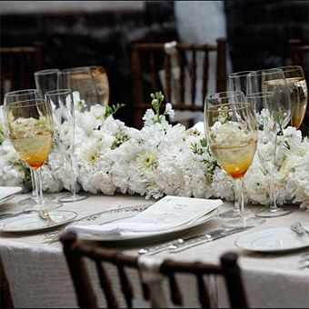 Brides Magazine: White Winter Wedding Flower Ideas  --  A long arrangement of carnations, wax flowers, stock and chrysanthemums runs the length of the table at this winter wedding. Beautiful Blooms    Photo: Marie Labbancz