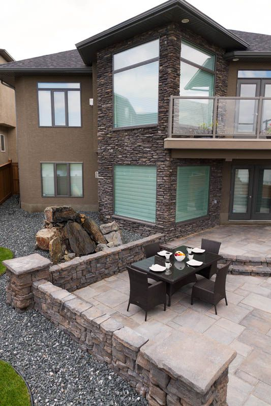 This Dimensional Flagstone patio with Belvedere Walls complement the brown tones of this majestic house