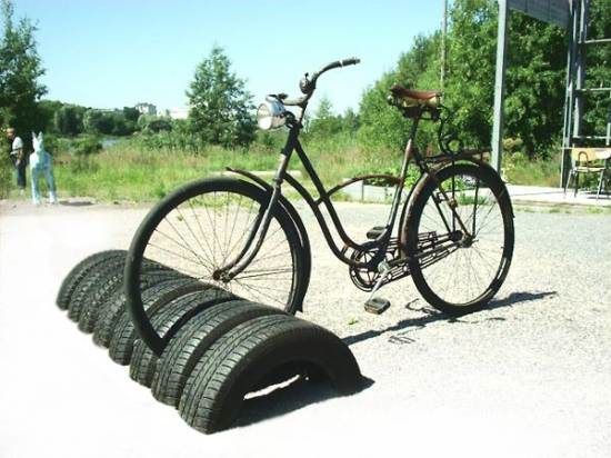 Bikestand made of tires, upcycle, green, tires are free (yes free) at the local tire shop...  could also use the spray paint that can be used on anything (indoor or outdoor) bright colors... this is a great green upcycle recycle, cool project, great one for scouts to do as a project... won't rust either... cool beans...