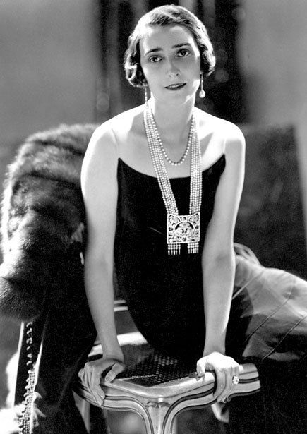 """A """"sautoir,"""" or a long, glamourous necklace that is punctuated in a large anchoring fixture such as a tassel, was a high-end staple of the 20s. The silhouette is evoked in this Cartier piece from 1928: five strands of pearls are yoked together with a diamond-and-ruby square. It's worn over a black Chanel dress."""