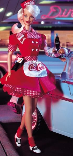 """1999. Pop Culture. COCA-COLA Barbie Series. Coca-Cola Barbie Doll (Waitress). COKE red and white uniform with matching gingham print trim. COCA-COLA trademarks adorning her apron, waitress cap and """"bottle-top"""" serving tray. Front of her uniform sports a Barbie monogram and cute little attached gingham print hankie.Wears black and white saddle shoes. Writing tablet. Car not included. Doll holds tray in right hand"""