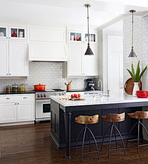 All white kitchen, white subway tiles, dark island, accents of red and **low back beach wood chairs