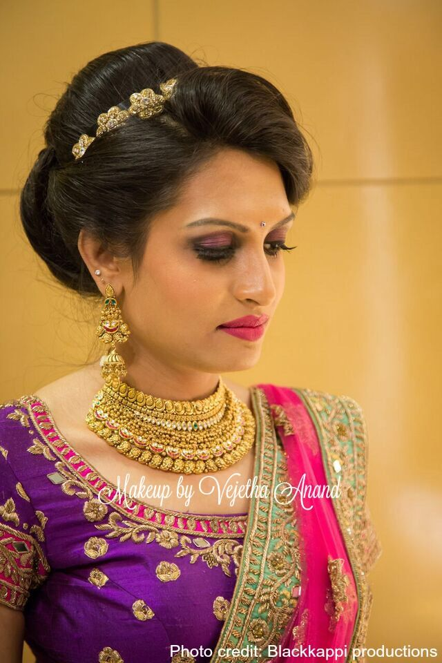 Indian bride Akshaya wears gorgeous pink and purple bridal lehenga and jewelry for her Reception. Makeup and hairstyle by Vejetha for Swank Studio. Gold bridal jewellery. Bridal hair. Hairstyle. Pink lips. Lehenga love. Eyemakeup.  Find us https://www.facebook.com/SwankStudioBangalore