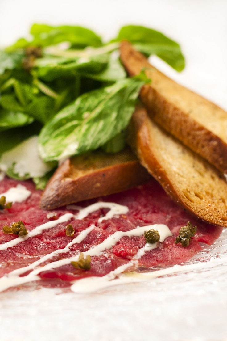 Beef carpaccio with arugula, shaved parmesan, fried caper served with ...