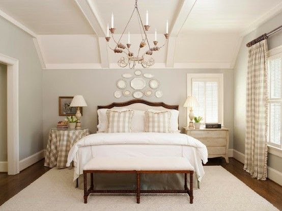 Susie Harris: Buffalo Gal .  Bed centered on wall with asymmetrical windows. Buffalo plaid curtains and pillows