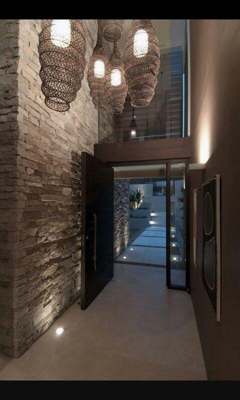 entrada moderna con doble altura y suelo del jardin con losas