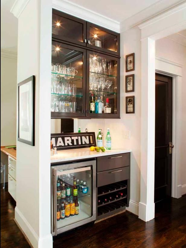 Custom-built wet bar, built-in wine storage, and custom-built lighted glass cabinets for the mini bar storage. Martini sign against backsplash