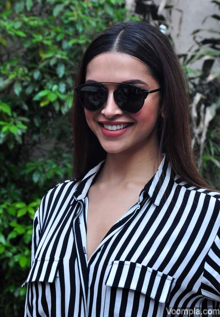 Deepika Padukone looks hot in a black and white striped by Custom Made. She completes her look with black sunglasses, pink lips and a centre part hairstyle. via Voompla.com