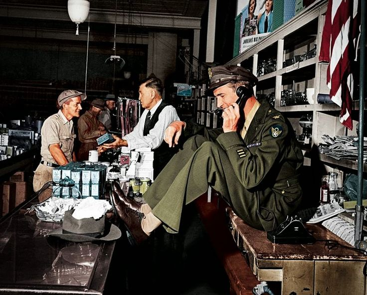 WWII colorized ~ While his father chats with a customer at the hardware store, a uniformed Jimmy Stewart sets up a date to go fishing, 1945. (Colorized by John Gulizia from America)