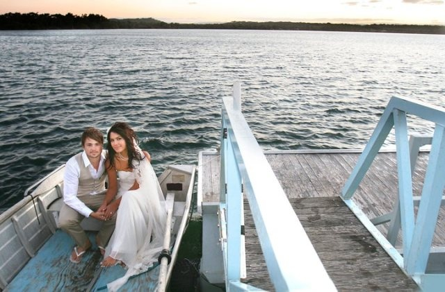 Mitch and Carol in a boat back to the main land at their Sandon River barefoot beach wedding.
