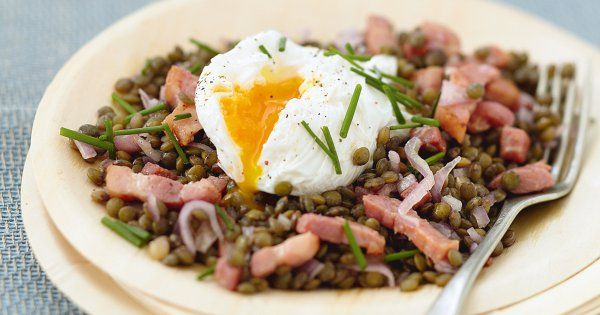 Cette salade tiède de lentilles vertes aux lardons et œufs pochés est facile à réaliser et à faible coût. Découvrez notre recette pas à pas pour réussir la recette classique et inratable aux légumineuses!