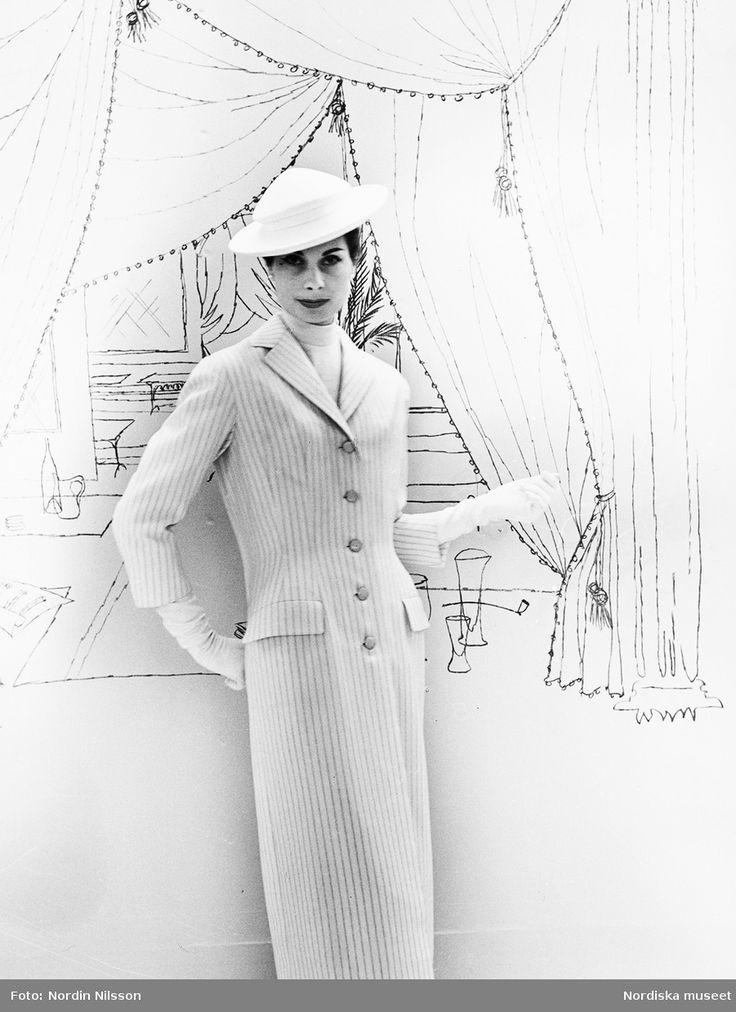 Original Balmain, 1955. Modell i ljus, randig kappa, vit hatt och vita handskar. Tecknad bakgrund. Foto: Nordin Nilsson