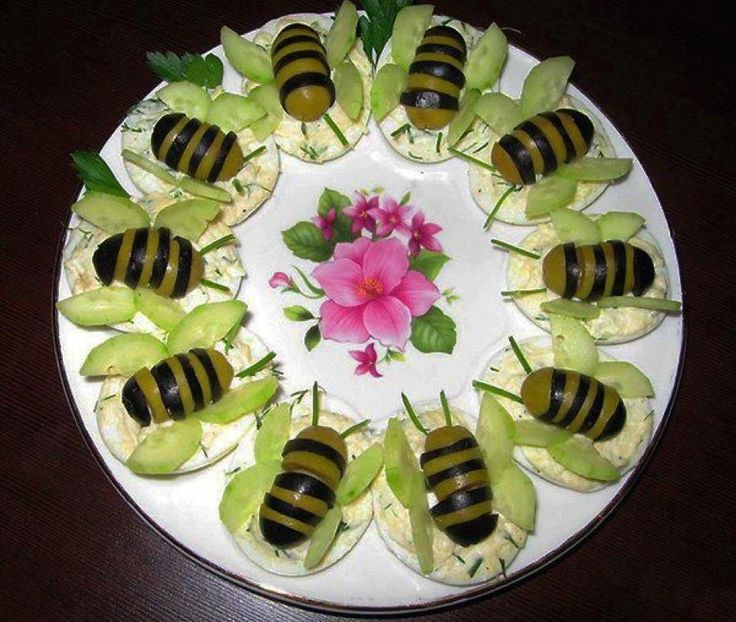 Bug olives (slices of green and black olive) with cucumber wings, with a schmear of cream cheese on a rice cracker to hold all in place.
