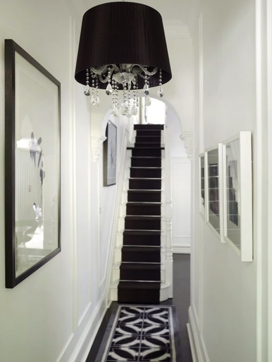 soft white walls dark hardwood floors and black and white geometric rug runner white stairways and bannister with black runner