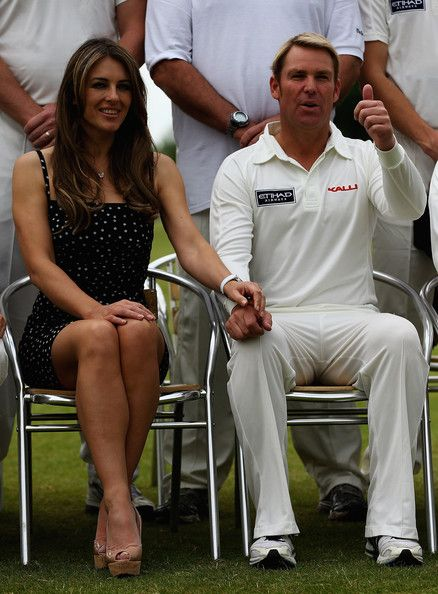 Elizabeth Hurley Photos Photos - Elizabeth Hurley and Shane Warne look on during the Shane Warne's Australia vs Michael Vaughan's England T20 match at Circenster Cricket Club on June 9, 2013 in Cirencester, England. - Shane Warne's Australia vs Michael Vaughan's England T20 match