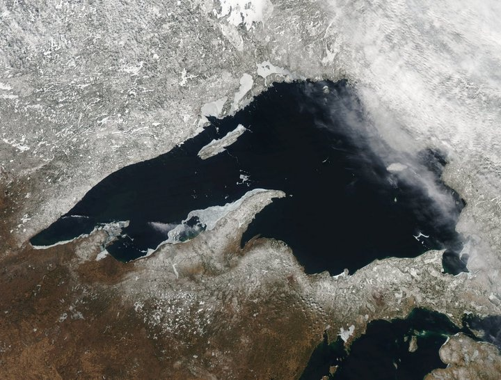 Sattelite photo of Lake Superior surrounded by snow.  The Keweenaw Peninsula juts straight up just below the prominent Isle Royale Island.