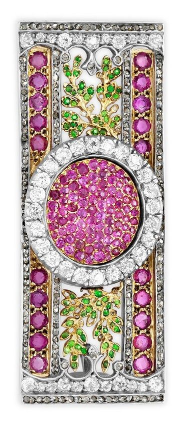 An Antique silver, 14k gold, diamond, demantoid garnet and ruby brooch. The elaborate rectangular plaque centring pavé-set rubies amid an oval old European-cut diamond frame, further decorated with demantoid garnet foliate motifs and ruby and rose-cut diamond borders, mounted in silver and 14k gold, 5.7 x 2.1cm. #antique #brooch