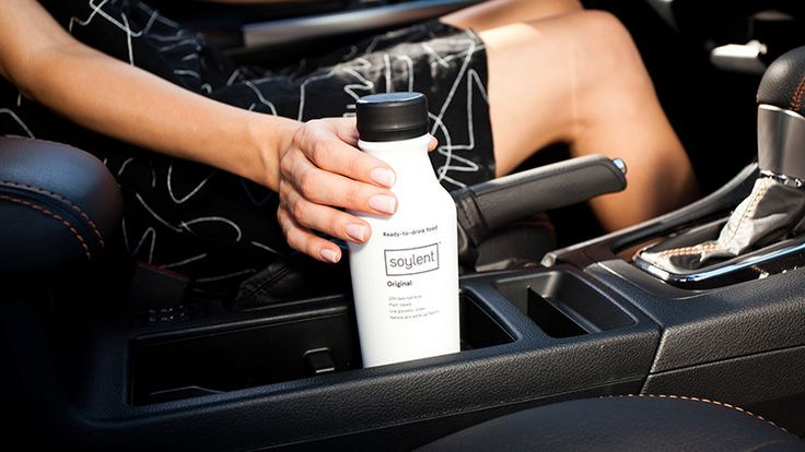 Person holding Soylent Drink in the car.