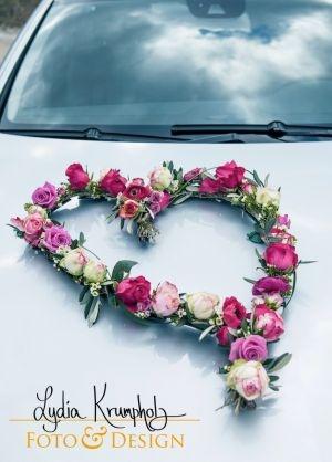 Herzförmiger Blumenschmuck auf einem Brautauto. Heart-shaped flowers on a car.