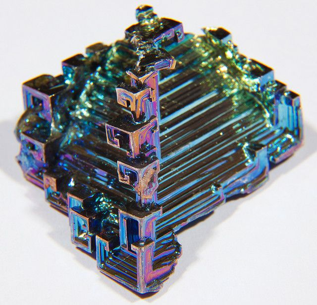 117: 83 Bi 铋 Bismuth, possibly from Arabic bi ismid, meaning 'having the properties of antimony'. It is a brittle metal with a silvery white color but is often seen in air with many iridescent refraction hues of its oxide surface, and the most naturally diamagnetic element and has one of the lowest values of thermal conductivity among metals. It is slightly radioactive. There is an increasing use of bismuth alloys as a replacement for lead.
