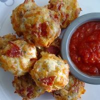 Pizza Muffins  3/4 C. flour  3/4 tsp. baking powder  1 Tbs. Italian seasoning  pinch of salt  pinch of red pepper flakes  3/4 C. whole milk  1 egg, beaten  1 C. mozzarella cheese, shredded  1/4 C. Parmesan cheese, grated  1 C. pepperoni  1/2 C. pizza sauce