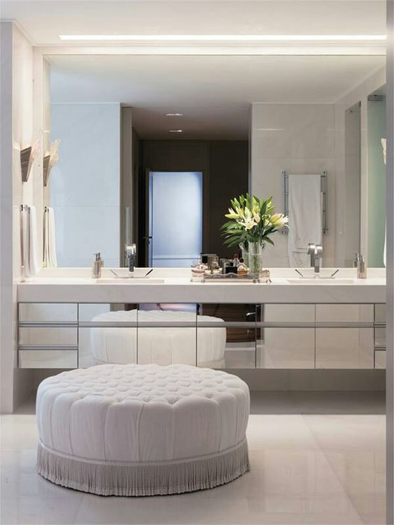 a mirror wall, mirrored cabinets and white statuary marble on the wall and on the floor