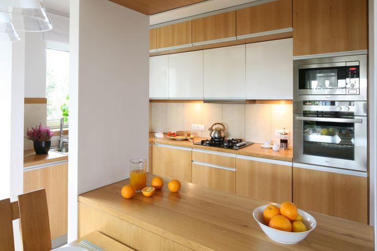 W wąskiej i niedużej kuchni zdecydowano się na dwa rzędy szafek górnych - w obu zamontowano oświetlenie doświetlające strefę roboczą. Projekt Marcin Lewandowicz. Fot. Bartosz Jarosz