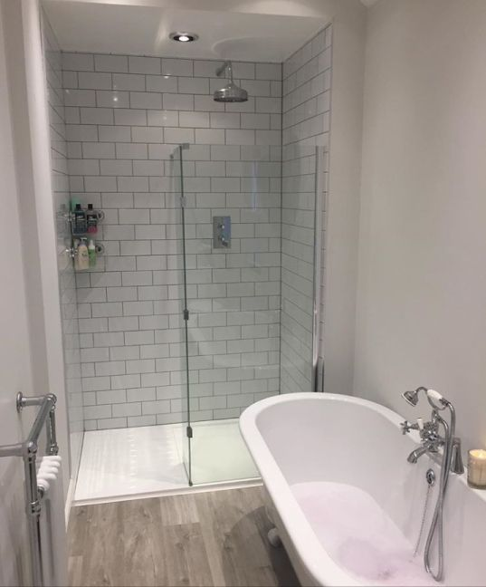 The walk-in shower enclosure has been tiled head to toe with white metro tiles. The shower set-up includes a large fixed shower head and concealed valve controls.